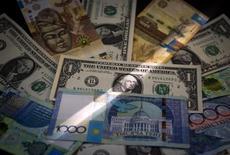 Купюры тенга и доллара США. Алма-Ата, 21 августа 2015 года. Глава Национального банка Казахстана Данияр Акишев после более чем 45-процентного падения национальной валюты заявил, что тенге должен консолидироваться на нынешних уровнях при условии сохранения цен на нефть около $30-40 за баррель. REUTERS/Shamil Zhumatov
