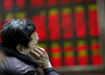 Foto de archivo de un hombre mirando un tablero electrónico que muestra la información de las acciones, en una correduría en Pekín. 17 de diciembre de 2015. El referencial CSI300 de las principales acciones que cotizan en Shanghái y Shenzhen cortó una racha de cuatro días de avances el miércoles, luego de que una caída al final de la sesión del índice ChiNext, dominado por los valores de pequeña capitalización, agrió la confianza de los inversores. REUTERS/Kim Kyung-Hoon/Files