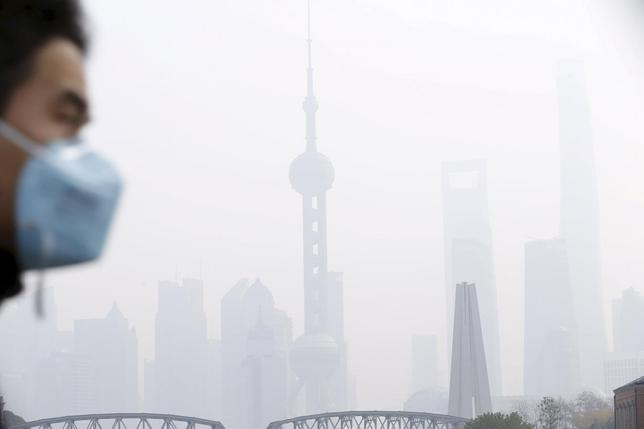 A man wearing a face mask walks on a bridge in front of the financial district of Pudong amid heavy smog in Shanghai, China, in this December 15, 2015 file photo. To match CHINA-POLLUTION/ REUTERS/Aly Song/Files