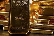 Слитки золота в хранилище ProAurum в Мюнхене. 3 марта 2014 года. Цены на золото стабильны на фоне растущего курса доллара и снижения цен на нефть, и рынок завершит спадом третий год подряд. REUTERS/Michael Dalder