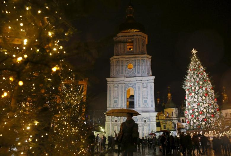 People walk past Christmas trees near the Bell tower of the Cathedral of St. Sophia in central Kiev, Ukraine, December 22, 2015. REUTERS/Valentyn Ogirenko