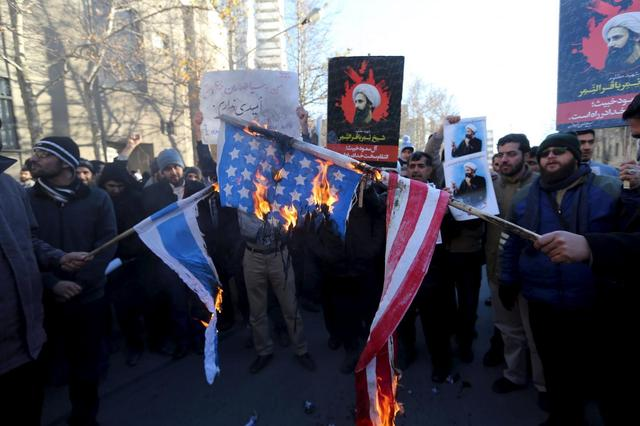 Iranian protesters holding pictures of Shi'ite cleric Sheikh Nimr al-Nimr burn a U.S. flag (R) and an Israeli flag during a demonstration against the execution of Nimr in Saudi Arabia, outside the Saudi Arabian Embassy in Tehran January, 3, 2016. REUTERS/Raheb Homavandi/TIMA