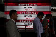 El Ibex-35 se desplomó el lunes en su primera jornada del año y amplió así las caídas con las que cerró el año 2015, contagiado por la desaceleración económica de China, tras unos débiles datos manufactureros. En la imagen, varias personas pasan frente a una pantalla con cotizaciones en Hong Kong, el 4 de enero de 2016. REUTERS/Bobby Yip