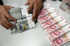 Funcionário movimenta notas de dólar e de iuan em agência do Banco da China em Taiyuan, na China. REUTERS/Jon Woo