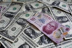 Un billete de 50 pesos mexicanos sobre un montón de billetes de un dólar en una ilustración fotográfica realizada en Ciudad de México, jul 6, 2015. Las monedas de América Latina continuarían sufriendo caídas y volatilidad esta semana, tras arrancar el año golpeadas por una nueva depreciación inesperada del yuan chino. REUTERS/Edgard Garrido