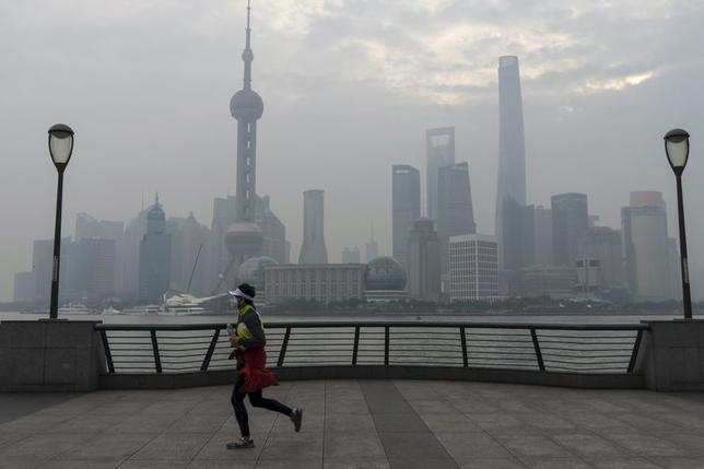 A jogger wearing a mask runs along the bund near the Huangpu river across the Pudong New Financial district, amid heavy smog in Shanghai, China, January 4, 2016. REUTERS/Stringer