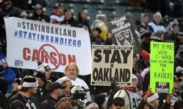 "Dec 24, 2015; Oakland, CA, USA; Spectators hold signs reading ""Stay in Oakland"" and ""Stay in San Diego"" in reference to the San Diego Chargers and the Oakland Raiders proposed move to Los Angeles during an NFL football game at O.co Coliseum. Mandatory Credit: Kirby Lee-USA TODAY Sports"