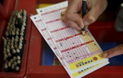 A person fills out numbers on a Powerball ticket   in Bethesda, Maryland January 8, 2016.   REUTERS/Gary Cameron