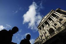 Прохожие у здания Банка Англии. Лондон, 16 января 2014 года. Регуляторы Банка Англии полагают, что недавнее падение цен на нефть немного снизит британскую инфляцию в ближайшие месяцы, но пока не могут сказать, будет ли это влияние продолжительным. REUTERS/Luke MacGregor