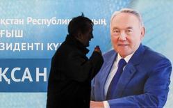 Человек проходит мимо плаката с изображением президента Казахстана Нурсултана Назарбаева. Алма-Ата,, 30 ноября 2015 года. Экспортирующий нефть Казахстан может сократить траты из казны в этом году и снизить прогноз роста ВВП из-за падения цены черного золота, сообщили члены правительства, предупредив, что нефть может оставаться дешевой десятилетиями. REUTERS/Shamil Zhumatov