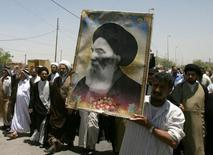 Iraqis carry a poster of top Shi'ite cleric Grand Ayatollah Ali al-Sistani during a demonstration in Najaf, 160 km (100 miles) south of Baghdad June 13, 2007.   REUTERS/Ali Abu Shish/Files