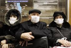 Пассажиры киевского метрополитена в медицинских повязках. 10 ноября 2009 года. За первую неделю января 15 человек умерли от гриппа на Украине - в полтора раза больше, чем за три предыдущих месяца, сообщил министр здравоохранения, добавив, что в большинстве смертей виноват свиной грипп H1N1. REUTERS/Konstantin Chernichkin