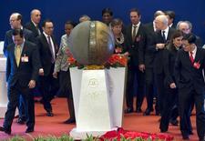 El presidente chino Xi Jinping lanzó el sábado en una pródiga ceremonia un nuevo banco internacional que competirá con el Banco Mundial que encabeza Estados Unidos, en un intento de Pekín por cambiar las reglas no escritas del financiamiento internacional al desarrollo. En la imagen, representantes de los países fundadores del Banco Asiático de Inversión en Infraestructuras caminan alrededor de una escultura presentada en la ceremonia de inauguración de la entidad en Pekín, el 16 de enero de 2016. REUTERS/Mark Schiefelbein/Pool