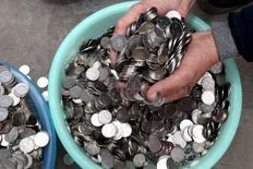 El banco central de China se está preparando para elevar el coeficiente de reservas requerido para los depósitos en yuanes offshore a partir del 25 de enero, iniciativa que marca el último intento para frenar la especulación sobre la divisa china, dijeron tres fuentes que han visto el documento que detalla el cambio. En la foro, un himbre sumerge las manos en una colección de monedas de 1 yuan en Zhengzhou, China, el 11 de enero 2016.  REUTERS/Stringer