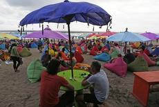 Las llegadas de turistas internacionales crecieron el año pasado un 4,7 por ciento, hasta 1.184 millones, según el ultimo informe de la Organización Mundial del Turismo (OMT). En la imagen, un turista bebe una botella de cerveza durante una puesta de sol en la playa de Seminyak, cerca de Kuta, en la isla de Bali, 3 de marzo de 2015. REUTERS/Beawiharta (INDONESIA - Tags: SOCIETY TRAVEL) - RTR4RUWX