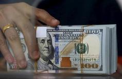 Un empleado de una casa de cambio sostiene un fajo de billetes de 100 dólares estadounidenses, en Yakarta, 8 de octubre de 2015. Una recuperación mínima de los mercados bursátiles contribuía a un avance del dólar frente al euro y al franco suizo el lunes. REUTERS/Beawiharta