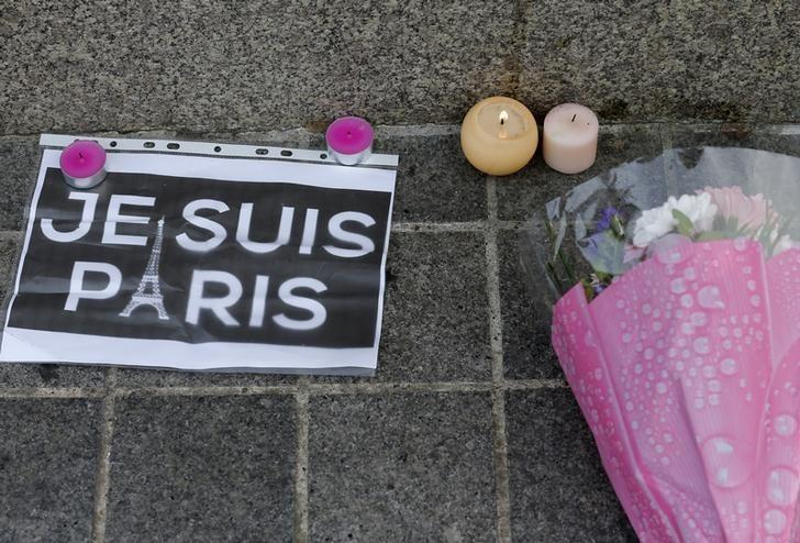 Candles, flowers and a leaflet with the slogan ''I am Paris'' are left in tribute to victims of Paris attacks in central Strasbourg, France, November 14, 2015. REUTERS/Vincent Kessler/Files