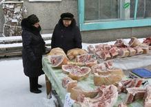 Женщины торгуют мясом в Красноярске. 12 января 2016 года. Инфляция в России с 12 по 18 января 2016 года составила 0,2 процента, а с начала месяца достигла 0,5 процента, сообщил Росстат. REUTERS/Ilya Naymushin