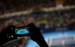 Imagen de archivo de un espectador tomando una fotografía durante un encuentro amistoso entre Roger Federer y Thomaz Belluci en Sao Paulo, dic 6, 2012. El auge de los dispositivos móviles está transformando las apuestas deportivas a nivel global más rápido de lo que los reguladores pueden reaccionar, inundando la industria con dinero y contribuyendo potencialmente a crear escándalos de corrupción como el que está sacudiendo al tenis, dijeron expertos.   REUTERS/Nacho Doce