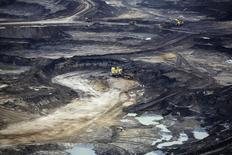 Giant dump trucks are loaded with raw tar sands at the Suncor tar sands mining operations near Fort McMurray, Alberta, September 17, 2014.  REUTERS/Todd Korol