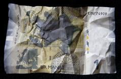 Банкнота номиналом один азербайджанский манат на фотоиллюстрации, сделанной в Тбилиси 15 января 2016 года. Азербайджан, пытающийся справиться с последствиями падения нефти - обрушившего доходы, обвалившего манат и выведшего на улицы недовольных  - ждет скачка инфляции и возобновит выпуск облигаций для латания дыр в бюджете, сообщили власти. REUTERS/David Mdzinarishvili - RTX22JS5