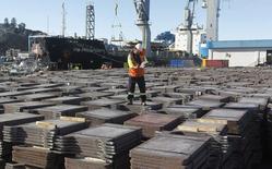 Un trabajador revisa un cargamento de cobre en el puerto de Valparaíso, Chile, ene 25, 2015. Los precios promedio del cobre bajarían este año a su menor nivel en más de una década, en vista del débil crecimiento de la demanda en el mayor consumidor de metales del mundo, China, y en medio de un superávit de existencias, indicó un sondeo de Reuters entre analistas.  REUTERS/Rodrigo Garrido