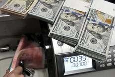 Служащий Bank of China считает доллары и юани при помощи специального аппарата.  Доллар немного ослаб во вторник, хотя основные валюты остались вблизи недавних значений, так как инвесторы сохраняли осторожность накануне двухдневного заседания ФРС, которое начнётся во вторник. REUTERS/Jon Woo