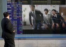 Un hombre una pantalla electrónica con información bursátil, afuera de una correduría en Tokio, Japón. 20 de enero de 2016. Las bolsas de Asia retrocedían el martes, en momentos en que los temores a una desaceleración de la economía mundial no muestran señales de disminuir y ante un nuevo desplome en los precios del petróleo. REUTERS/Toru Hanai