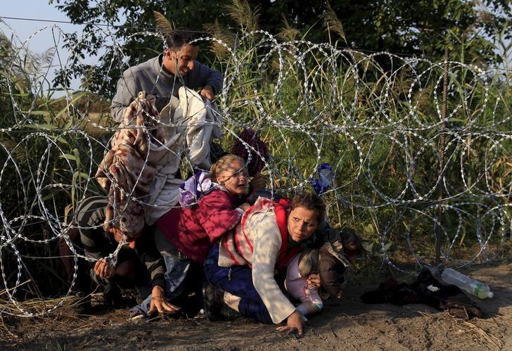 Syrian migrants cross under a fence into Hungary at the border with Serbia, near Roszke, August 27, 2015.  REUTERS/Bernardett Szabo