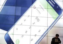 Мужчина пользуется телефоном на фоне рекламы Samsung в штаб-квартире компании в Сеуле 18 декабря 2015 года. Технологический гигант Samsung Electronics планирует запуск программы обмена старых смартфонов на новые, аналогичную появившейся у Apple в прошлом году, сообщило южнокорейское издание Electronic Times в среду со ссылкой на неназванные источники.  REUTERS/Kim Hong-Ji