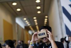 """A conference attendee looks through """"Cardboard,"""" a viewer that enables the user to view content from a smart phone in 3D, during the Google I/O developers conference in San Francisco, California May 28, 2015.  REUTERS/Robert Galbraith"""