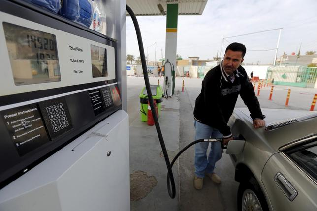 A man fills a car with fuel at a petrol station in Baghdad, January 26, 2016. REUTERS/Ahmed Saad