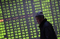 Un inversor camina junto a un tablero electrónico que muestra la información de las acciones, en una correduría en Hangzhou, China, 21 de enero de 2015. Las acciones chinas subieron más de un 3 por ciento el viernes y recuperaron parte de las pérdidas al final de una semana tumultuosa, pero anotaron su peor caída mensual desde la crisis financiera global. REUTERS/China Daily