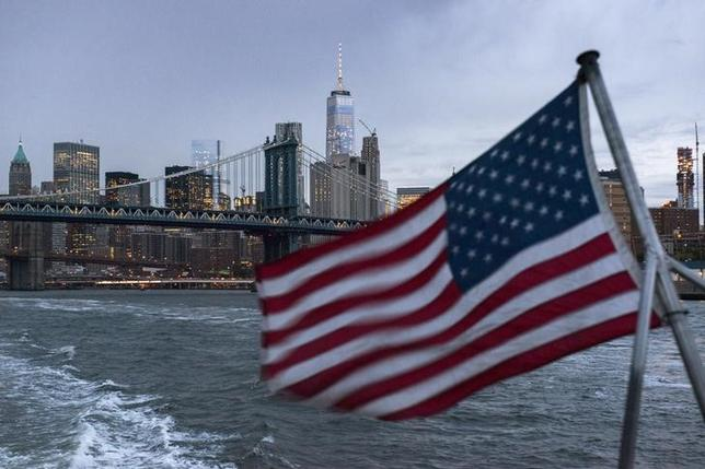 The Lower Manhattan skyline, One World Trade Center and Manhattan Bridge are seen in the background as a ferry with a U.S. flag cruises along the East River while carrying passengers (not pictured) to the 2016 Volkswagen Passat reveal in New York September 21, 2015.    REUTERS/Darren Ornitz