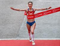 Liliya Shobukhova of Russia crosses the finish line to win the women's London marathon in London April 25, 2010.   REUTERS/Andrew Winning
