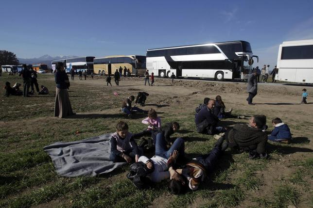 Migrants rest next to buses as they wait to cross the Greek-Macedonian border near the village of Idomeni, Greece, February 2, 2016. REUTERS/Alexandros Avramidis