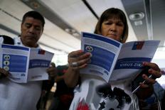 People read zika virus flyers from an information campaign by the Chilean Health Ministry at the departures area of Santiago's international airport, Chile January 28, 2016.  REUTERS/Ivan Alvarado