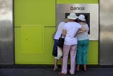 Las sentencias del Tribunal Supremo en las que rechazó la semana pasada dos recursos presentados por Bankia contra la anulación de la adquisición de sus acciones con ocasión de la colocación en bolsa en 2011 distinguen entre inversores institucionales y particulares. En la imagen, gente usa un cajero de Bankia en Sevilla, el 24  de junio de 2013. REUTERS/Marcelo del Pozo