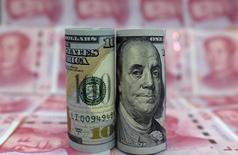 Банкноты доллара США и китайского юаня. Пекин, 21 января 2016 года. Доллар восстановил потери к иене и евро в четверг после ночного падения из-за комментариев одного из высокопоставленных представителей Федеральной резервной системы США. REUTERS/Jason Lee