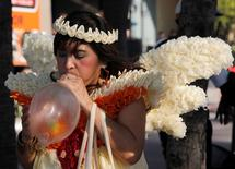 A member of the Population and Community Development Association, wearing a costume made of condoms, blows a condom during a march marking World AIDS Day in Pattaya, 150 km (93 miles) east of Bangkok December 1, 2011. REUTERS/Chaiwat Subprasom