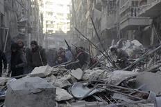 Местные жители изучают разрушения после авиаударов просирийских сил по укреплениям повстанев в аль-Шаар, районе провинции Алеппо, 4 февраля 2016 года. Командующий сирийской повстанческой группой, опирающейся на поддержку США, сказал в пятницу, что северный пригород провинции Алеппо полностью окружён войсками президента Башара Асада и их союзниками, а российская авиация продолжает интенсивные бомбардировки. REUTERS/Abdalrhman Ismail