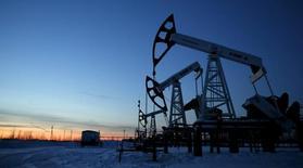 Насосы-качалки на Имилорском нефтяном месторождении, принадлежащем компании Лукойл. Цены на нефть разнонаправленны после снижения в начале торгов, завершая нестабильную неделю, когда цены порой менялись на 10 процентов в течение дня.  REUTERS/Sergei Karpukhin