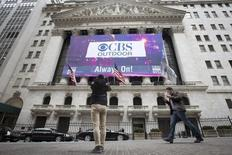 A man takes a photo of a CBS Outdoor banner displayed on the facade of the New York Stock Exchange celebrating the company's IPO, in New York March 28, 2014.  REUTERS/Brendan McDermid