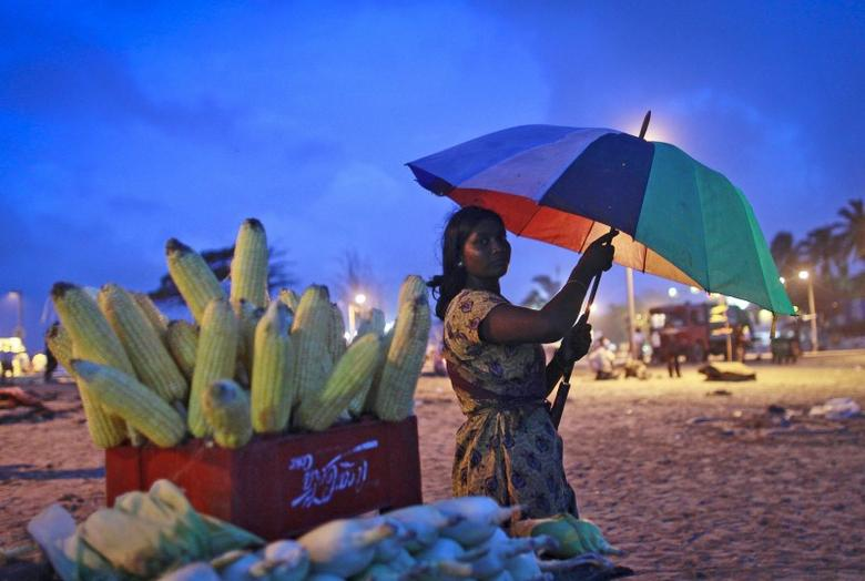 A woman selling grilled corn takes shelter under an umbrella as it rains on a beach in Mumbai in this July 11, 2012 file photo.    REUTERS/Danish Siddiqui/Files