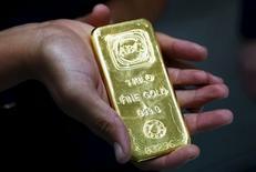 Una mujer sostiene una barra de oro de un kilogramo, en la sede de Australian Bullion Company, en Sídney, Australia. 19 de abril de 2013. El oro subía el martes, poniendo fin a dos días a la baja y recuperándose de una caída por debajo de 1.200 dólares la onza en medio de la debilidad de los mercados de acciones, lo que impulsaba el interés en el metal como refugio del riesgo. REUTERS/Daniel Munoz/Files
