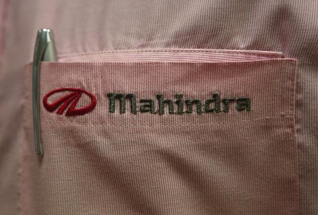 The logo of Mahindra & Mahindra Ltd is pictured on the pocket of a salesman's shirt as he poses inside the company's showroom in Mumbai in this file photo dated August 13, 2013. REUTERS/Danish Siddiqui