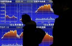 Пешеходы у брокерской конторы в Токио. 9 февраля 2016 года. Японские акции выросли в четверг после обнародования превысивших прогнозы экономических данных из США и роста цен на нефть, что помогло улучшить аппетиты глобальных инвесторов к риску. REUTERS/Yuya Shino