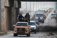 Боевики сопровождают гуманитарный конвой, движущийся в направлении селений аль-Фоуа и Кефрайа в провинции Идлиб 17 февраля 2016 года. Грузовики ООН за минувшие сутки доставили еду и медикаменты для десятков тысяч человек, страдающих от голода и дефицита лекарств в блокированных гражданской войной районах Сирии, воплощая план, выработанный на прошлой неделе мировыми державами.  REUTERS/Ammar Abdullah