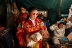 A Chinese opera actress carries her baby backstage before the start of a performance in Chinatown in Bangkok February 17, 2016. REUTERS/Jorge Silva
