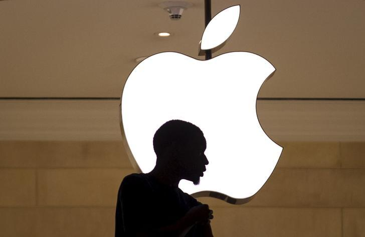 A customer stands beneath an Apple logo at the Apple store in Grand Central station in New York City July 21, 2015. REUTERS/Mike Segar